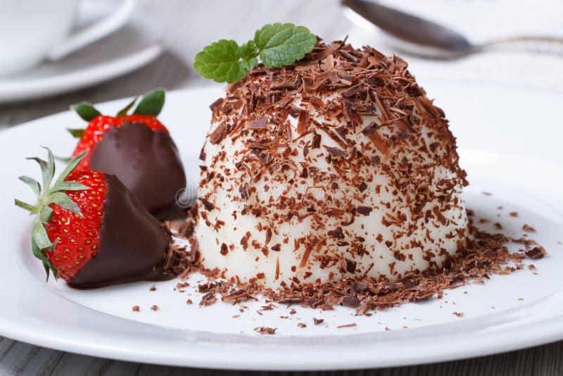 Panna cotta with dark chocolate and strawberries close-up. Italian dessert panna cotta with dark chocolate and strawberries close-up on the table. horizontal royalty free stock photos