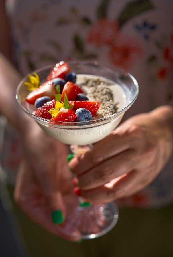 Panna cotta del dessert con il fiore della margherita in mani femminili Fragole e bacche fresche su fondo di legno, selettivo fotografia stock libera da diritti