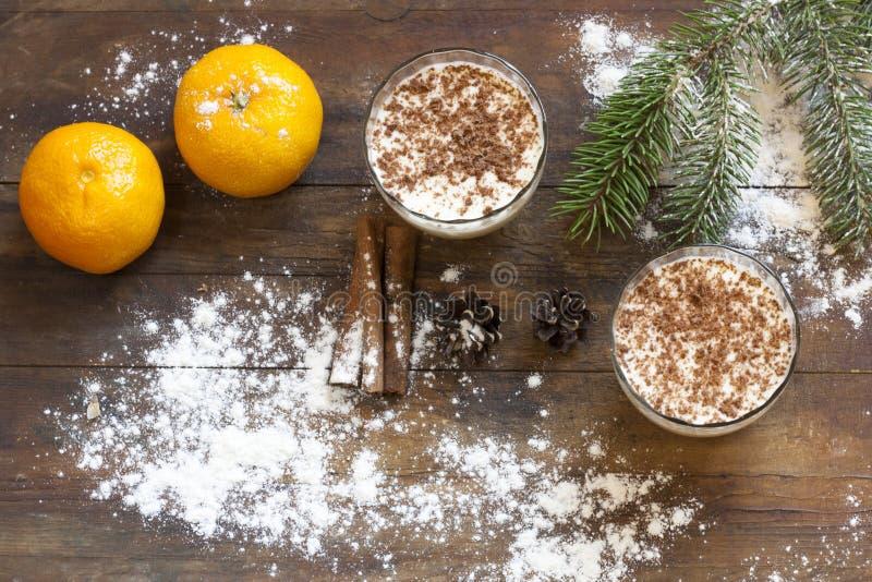 Panna cotta della vaniglia con cioccolato, i mandarini, i coni, la cannella ed i dadi in decorazione di Natale con l'albero di Na immagine stock