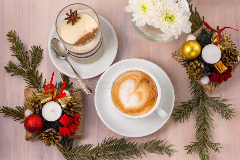 Panna Cotta met een kop koffie en Kerstmisdecoratie op een houten achtergrond stock afbeelding