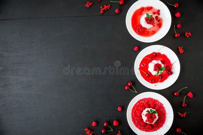 Panna-Cotta mit Fruchtsirup in einer Platte auf einem dunklen Hintergrund und geschmackvollen Beeren Flache Lage Beschneidungspfa stockfotos