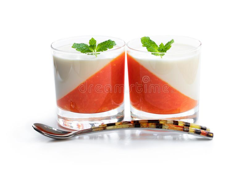 Panna cotta with orange jelly in clear glass isolated on white stock photo