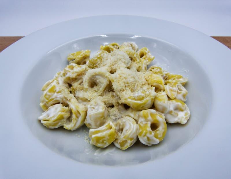 Panna do alla do Tortellini com Parmesão em uma placa branca, massa italiana imagens de stock royalty free