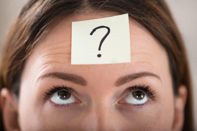Panna för affärskvinna` s med frågan Mark On Sticky Note arkivfoton