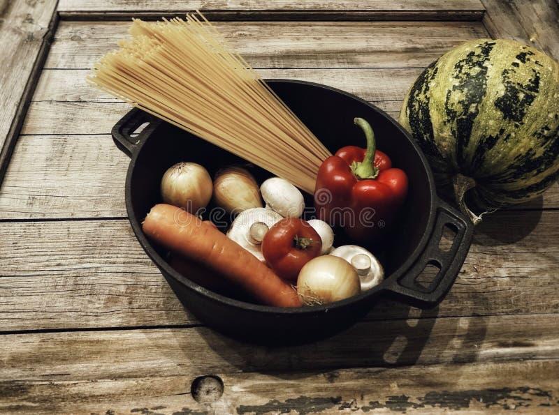 panna för närbild för ingrediens för mat för bakgrund för spagetti för champignons för tomater för pepparpumpapeppar wood royaltyfri foto