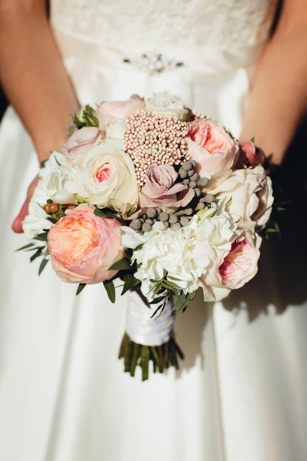 Panna młoda trzyma ślubnego bukiet różni kwiaty w jej rękach obrazy stock