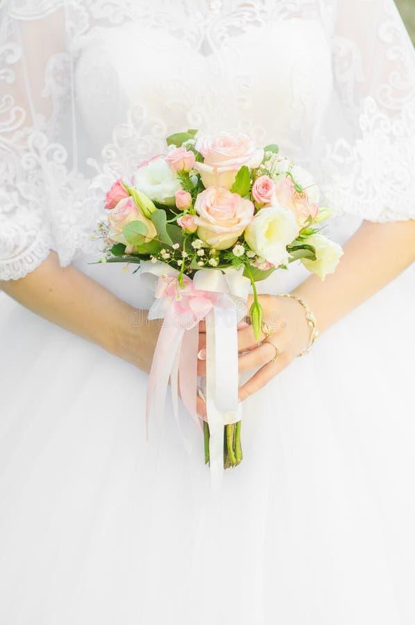 Panna młoda trzyma ślubnego bukiet w ona ręki biały różowe bukiet róże zdjęcie royalty free