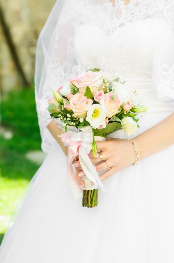 Panna młoda trzyma ślubnego bukiet w ona ręki biały różowe bukiet róże zdjęcia royalty free