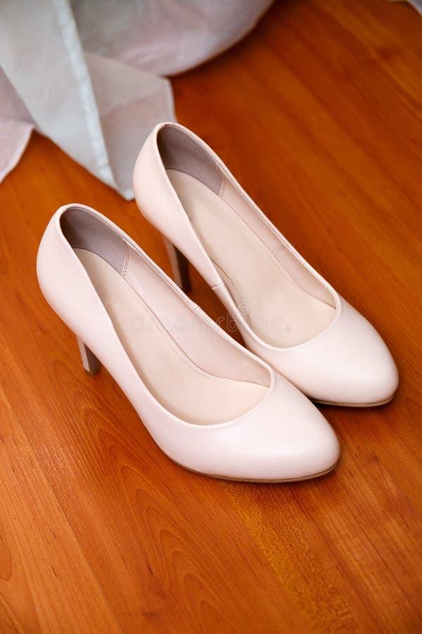 Panna młoda buty z złocistą obrączką ślubną na nim drewniany tło zdjęcie stock