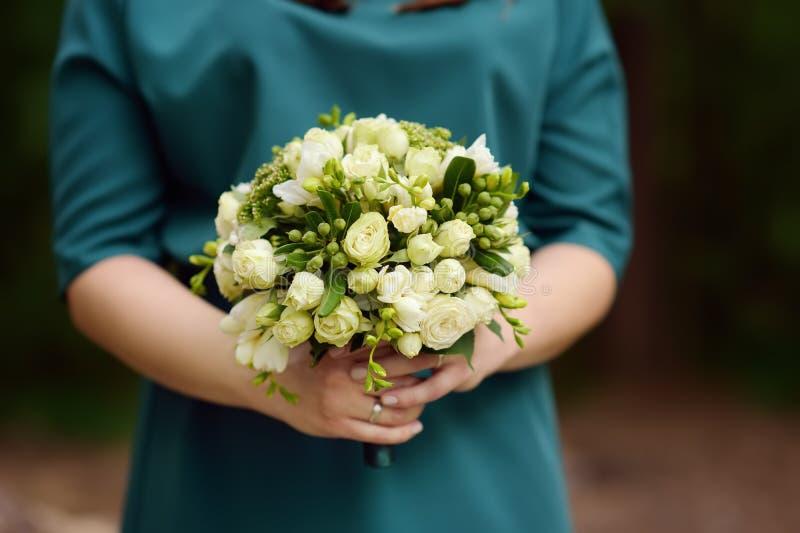 Panna młoda lub drużka trzyma eleganckich ślubów kwiaty fotografia stock