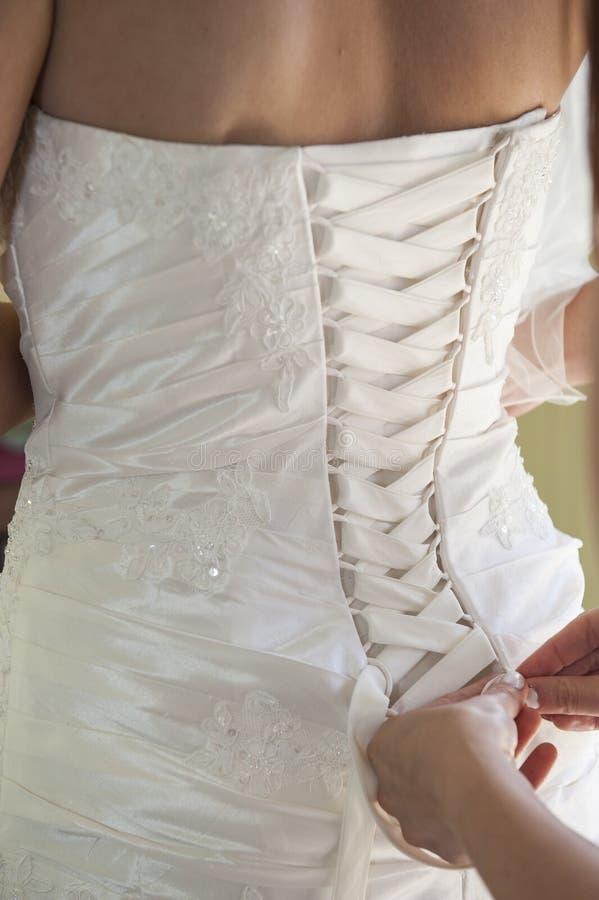Panna młoda ma jej suknię zasznurowywającą up zdjęcie stock