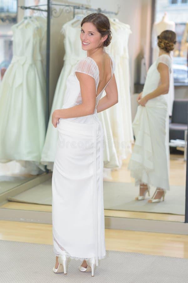 Panna młoda próbuje dalej ślubną suknię obraz stock