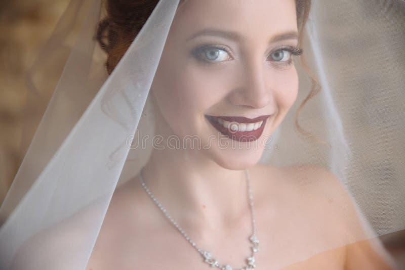 Panna młoda próbuje dalej przesłonę i ono uśmiecha się Piękna dziewczyna w ślubnej sukni ma zabawę i iść dostawać zamężną obrazy royalty free