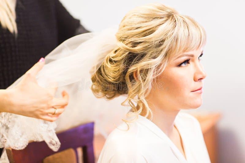 Panna młoda przy fryzjerstwo salonem robi ślubnemu pióropuszowi obraz royalty free