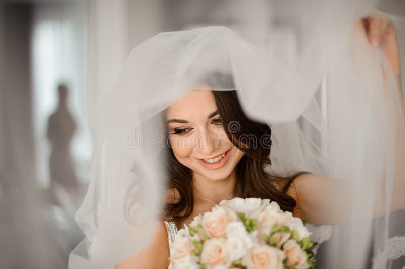 Panna młoda ranku przygotowanie Atrakcyjna i uśmiechnięta panna młoda w białej przesłonie z ślubnym bukietem obraz stock