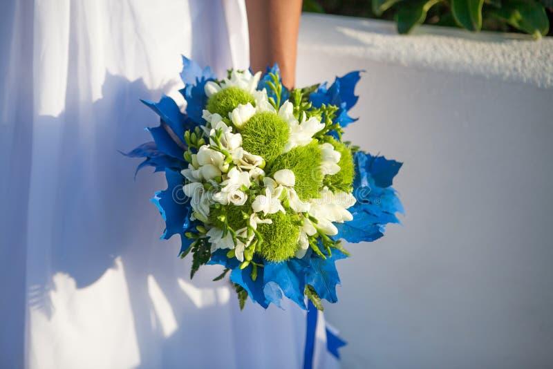 Panna młoda trzyma ślubnego bukiet w kolorach i błękitnym wystroju białych i zielonych fotografia stock