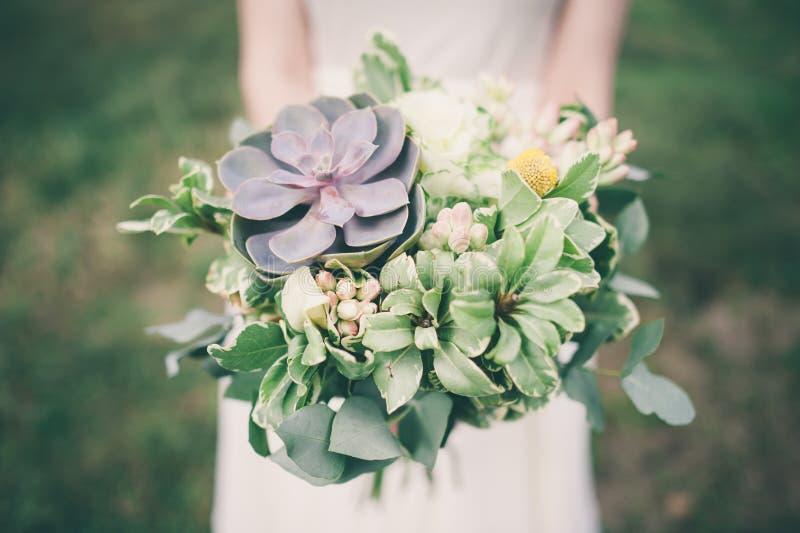 Panna młoda trzyma ślubnego bukiet z tłustoszowatymi kwiatami, obraz royalty free
