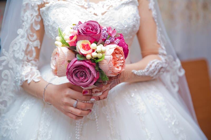 Panna młoda trzyma bukiet białe róże w jej rękach - wizerunek Bukiet w rękach panna młoda - wizerunek zdjęcia stock