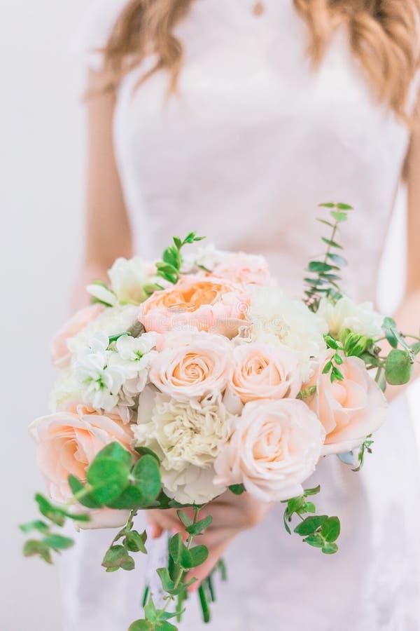 Panna młoda trzyma wspaniałego ślubnego bukiet w pastelowych kolorach peonie i róże zdjęcie royalty free