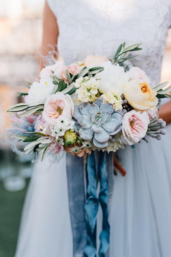 Panna młoda w błękitnej ślubnej sukni trzyma kolorowego ślubnego bukiet z zdjęcie stock