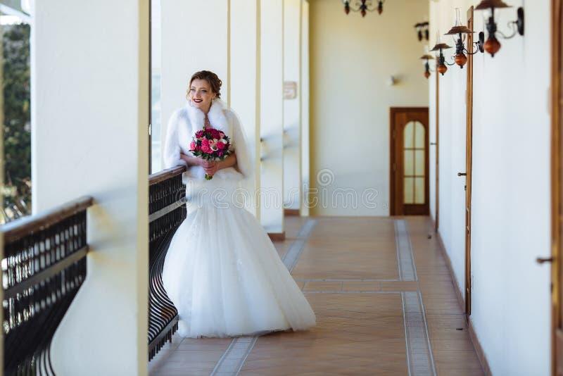 Panna młoda w białej sukni z ciasną spódnicą stoi na balkonie i podziwia naturę Dziewczyna trzyma a zdjęcie stock