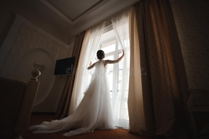 Panna młoda w białej sukni z pióropuszem otwiera zasłony zdjęcie royalty free