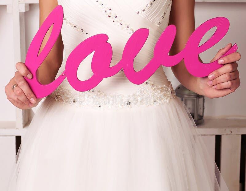 Panna młoda w eleganckiej ślubnej sukni mienia deco miłości obraz royalty free