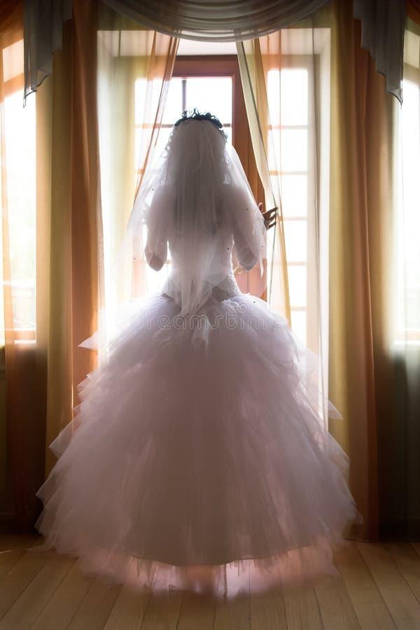 Panna młoda w okno otwiera zasłony obraz royalty free