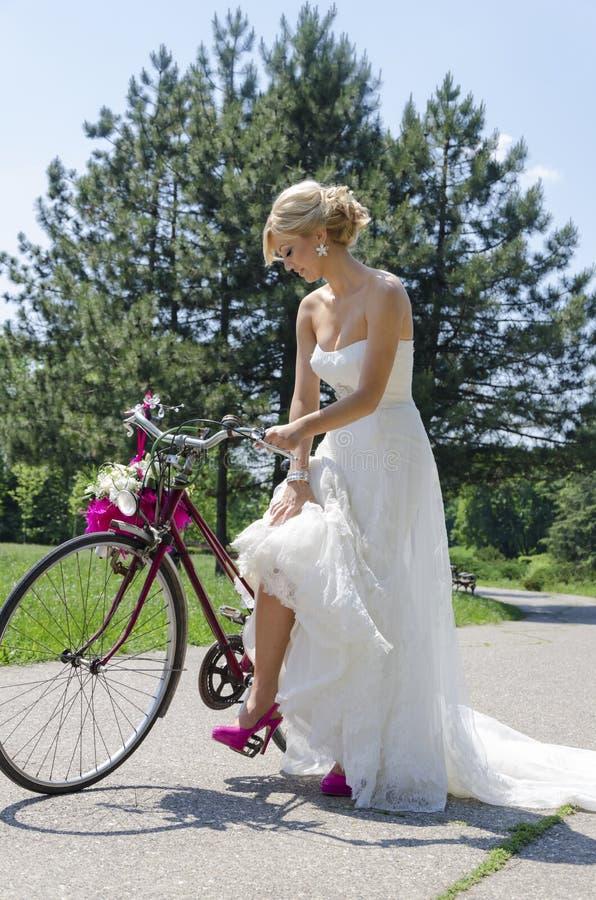 Panna młoda w purpurowych butach na rowerze zdjęcia stock