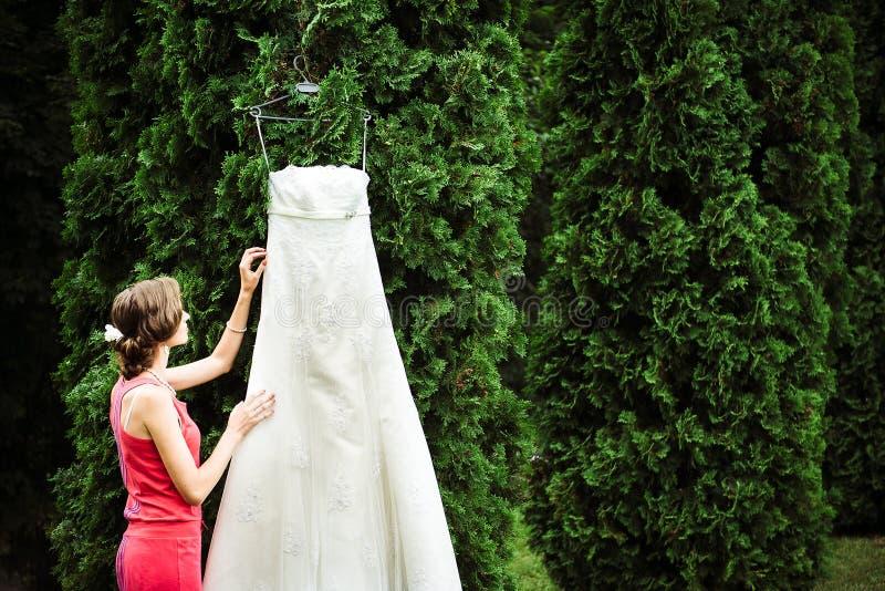 Panna młoda wewnątrz z jej włosianym robić macanie sukni obwieszeniem obraz stock
