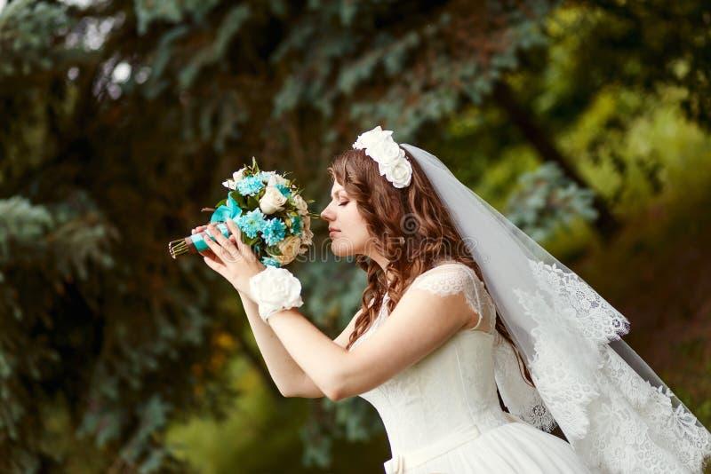 Panna młoda z kędzierzawym włosy i przesłoną trzyma pięknego bukiet w ona ręki obrazy stock