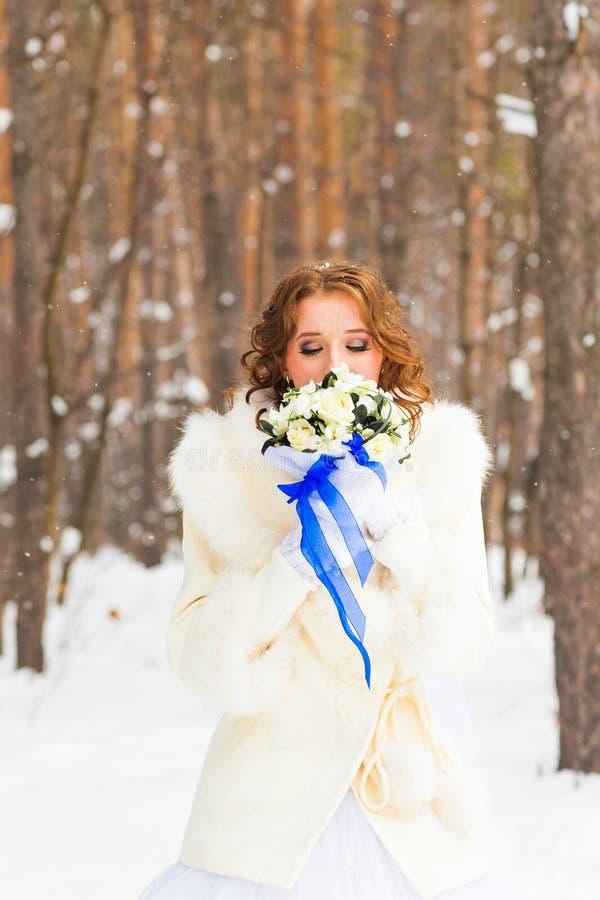 Panna młoda z kwiatu bukietem w zima lesie obrazy stock