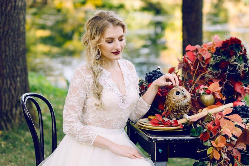 Panna młoda z sową Piękna uśmiechnięta panna młoda siedzi blisko słuzyć ślubu stołu z czerwonymi jesień liśćmi obraz stock