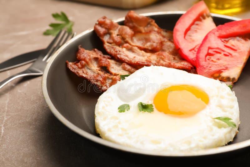 Panna med den stekte soliga sidan upp ägget, bacon och tomaten på tabellen arkivbild