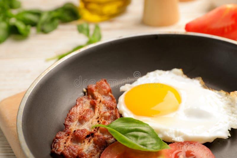 Panna med den stekte soliga sidan upp ägget och bacon på tabellen royaltyfria foton