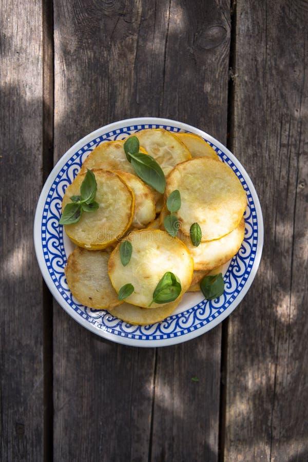 Pannan stekte zucchinistruvor, traditionella plana zucchinipannkakor med vitl arkivfoto