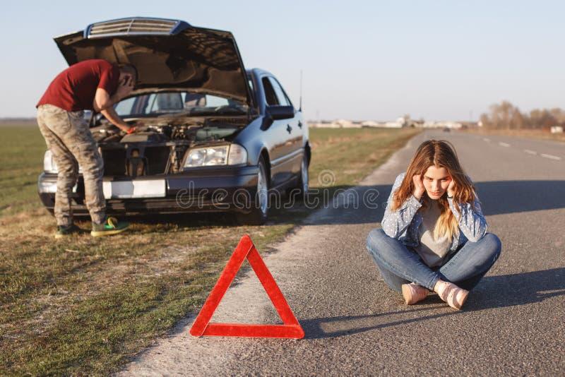 Panne à côté de route Le mâle essaye de réparer la voiture, appel par le téléphone portable dans l'aide de route, peut le ` t rés photographie stock