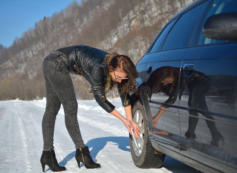 Panne de voiture d'hiver - jeune femme de mode essayant de fixer la voiture photo stock