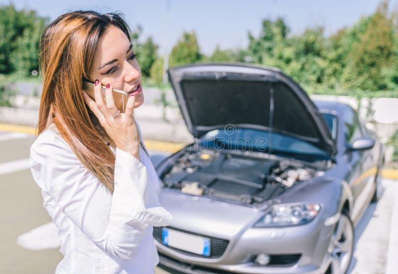 Panne de voiture jeune femme appelle l'aide au téléphone images stock