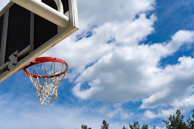Panneau arrière de basket-ball avec un anneau sur la rue et le ciel bleu images stock