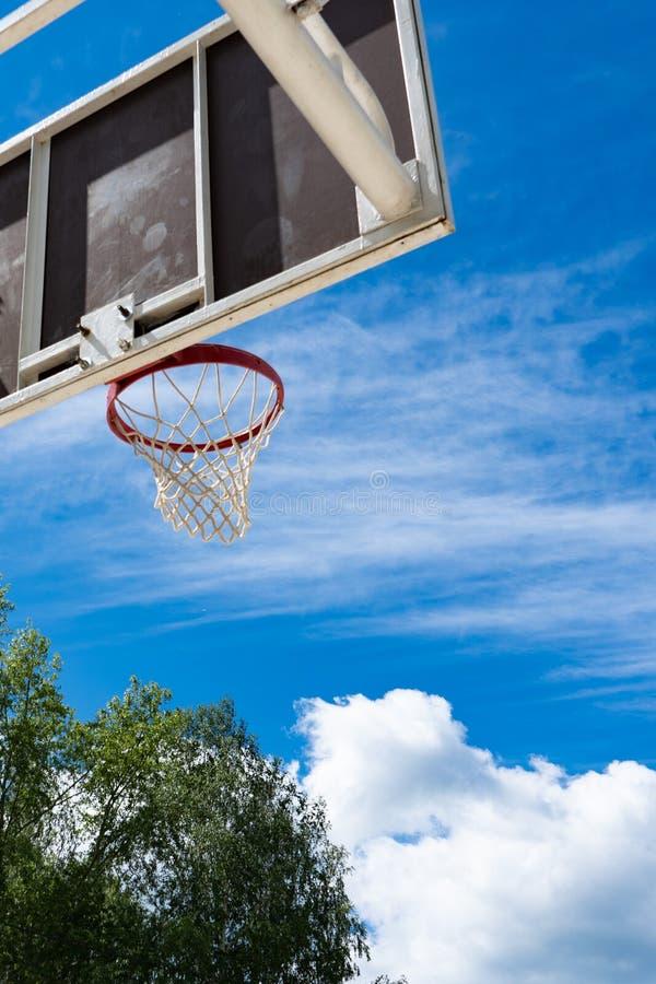 Panneau arrière de basket-ball avec un anneau sur la rue et le ciel bleu photo libre de droits