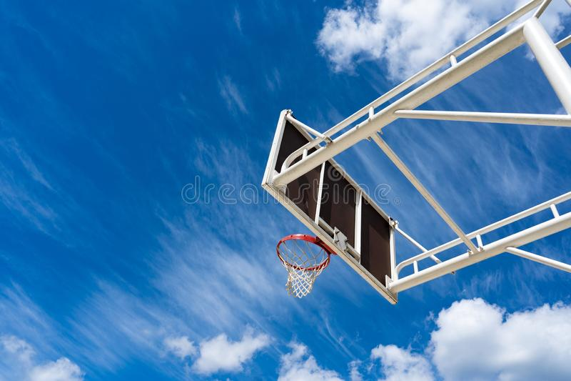 Panneau arrière de basket-ball avec un anneau sur la rue et le ciel bleu photographie stock