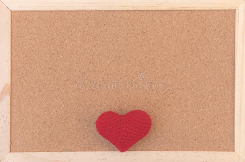 Panneau brun simple classique de liège avec le coeur de tricotage rouge en bas du cadre photos libres de droits