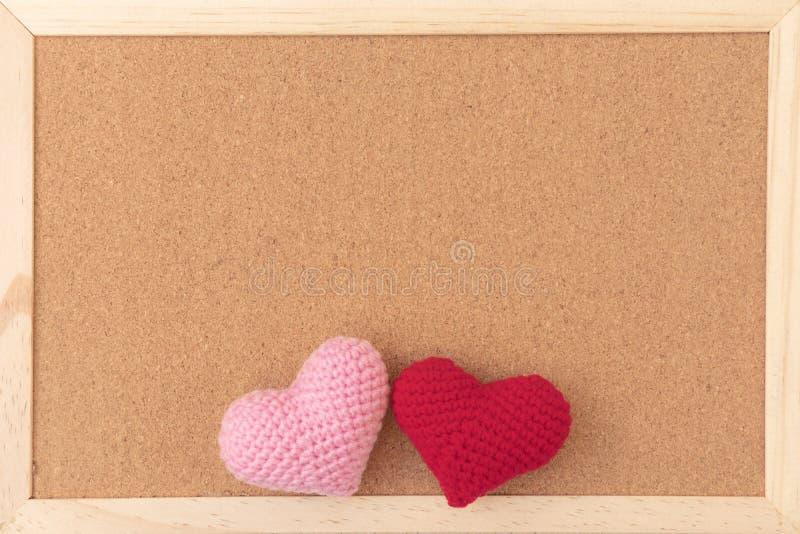Panneau brun simple classique de liège avec les coeurs de tricotage rouges et roses en bas du cadre images stock