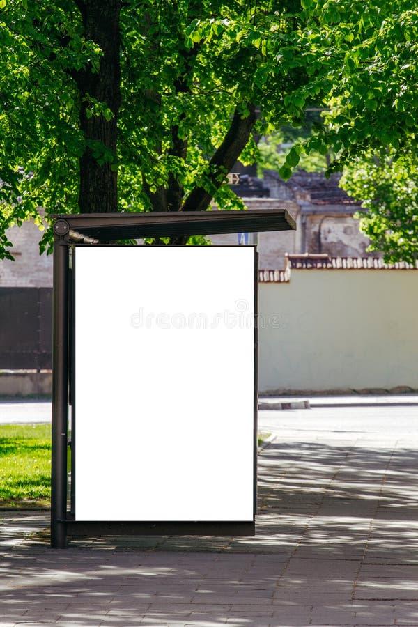 Panneau d'affichage blanc vide vertical à l'arrêt d'autobus sur la rue de ville images libres de droits