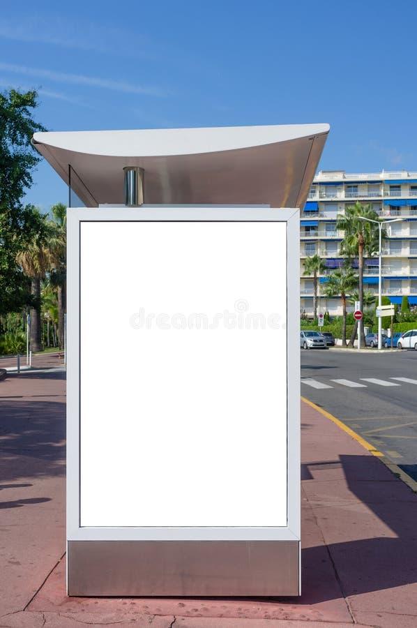 Panneau d'affichage blanc vide vertical à l'arrêt d'autobus sur la rue de ville Dans les bâtiments et la route de fond Voir les m photographie stock libre de droits