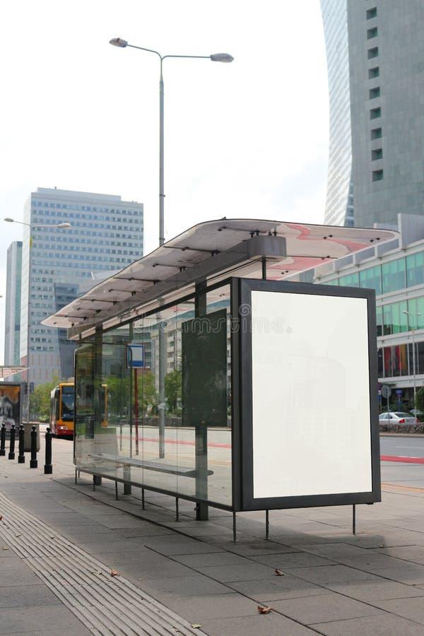 Panneau d'affichage blanc vide vertical de maquette sur la rue de ville d'arrêt d'autobus Dans les bâtiments et la route de fond  photos libres de droits