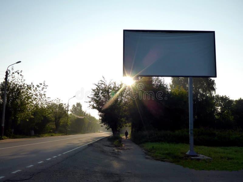 Panneau d'affichage tôt le matin sur une route vide image stock