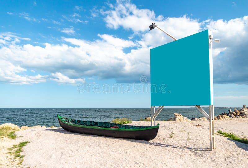 Panneau d'affichage vide bleu à côté d'un bateau de pêche local et en bois, sur le sable, au rivage de la Mer Noire Marea Neagra, photographie stock libre de droits