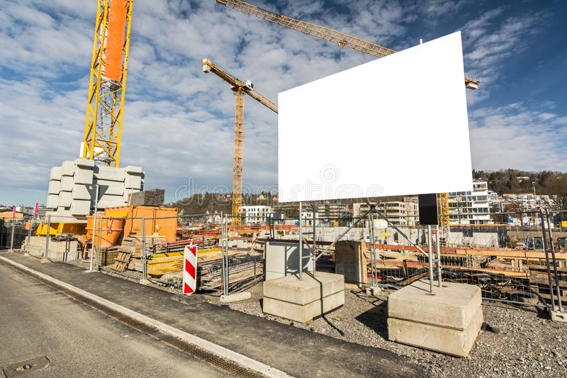 Panneau d'affichage vide devant des grues sur le grand chantier de construction photo stock